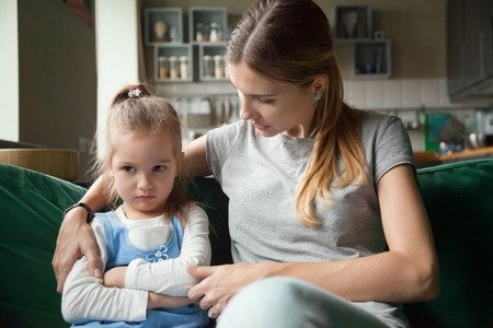Loving mother consoling or trying make peace with insulted upset stubborn kid daughter avoiding talk, sad sulky resentful girl pouting ignoring caring mom embracing showing support to offended child Stock Photo