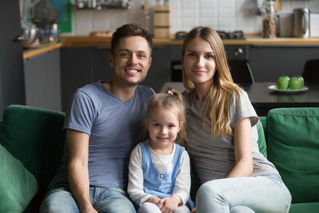 Portrait of happy healthy loving family of three concept, mom and dad posing with kid preschool daughter bonding together, young smiling parents sitting on sofa with child girl looking at camera Stock Photo