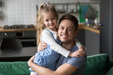 Portrait of happy dad hugging kid cute daughter looking at camera at home, smiling young daddy embracing cute girl expressing love and care, good single father posing with his child indoors concept
