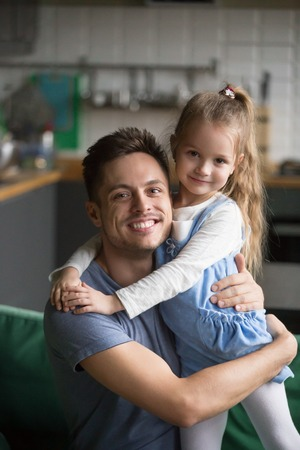 Vertical portrait of happy kid daughter embracing father at home, cute preschool girl hugging her smiling dad bonding looking at camera, caring daddy and little child good relationships concept