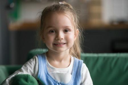 Porträt des niedlichen kleinen Mädchens drinnen, glückliches lustiges hübsches Kind mit aufrichtigem lächelndem Gesicht, das Kamera betrachtet, entzückendes positives fröhliches Kind, das zu Hause auf Sofa aufwirft, schöner Vorschulmodell-Kopfschuss