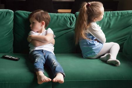 Zdenerwowane rodzeństwo chłopiec i dziewczynka dąsają się siedząc z rękami skrzyżowanymi na sofie i nie rozmawiają, dzieciaki, siostra brata, ignorujące się nawzajem po kłótni o wybór kanału telewizyjnego, konflikty dzieci i koncepcja rywalizacji Zdjęcie Seryjne