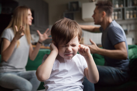 Frustrated kid son puts fingers in ears not listening to noisy parents arguing, stressed preschool boy suffering from mom and dad fighting shouting, family conflicts negative impact on child concept Stock Photo