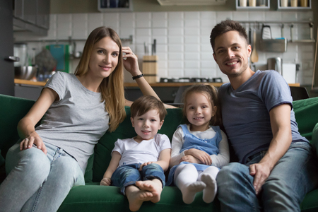 Portrait of happy parents with son and daughter sitting on comfortable sofa together, smiling loving family and cute kids looking at camera bonding on couch, children with mom and dad posing at home