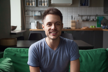 Smiling young man looking at camera sitting on sofa in the kitchen, millennial guy talking making video call, friendly vlogger speaking shooting videoblog at home, lifestyle vlog concept, headshot Stock Photo