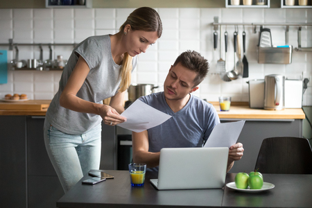 Serious millennial couple worried about high utility bills or rent payment reading papers in kitchen, confused husband and wife discussing bad news in bank loan document having debt financial problem