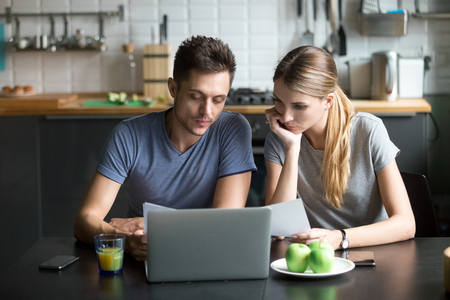 Young couple thinking of family budget planning with laptop and papers at home, filling internet application form on website or paying domestic utility bills documents online with banking software