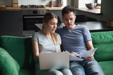 Worried couple confused reading bad news in bank loan documents or money debt calculating high domestic bills or rent payment checking papers with laptop, family discussing financial problems concept