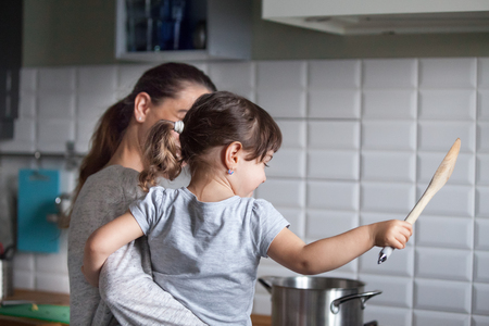 Rear view at mother holding happy excited child teaching little girl to cook in the kitchen, young mom and kid having fun while preparing food together, daughter helping mommy with dinner concept