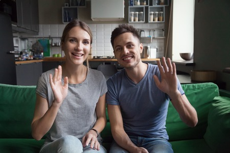 Smiling millennial couple waving hands sitting on kitchen sofa looking at camera making videocall, happy fit vloggers recording video blog at home, portrait, healthy food and lifestyle vlog concept