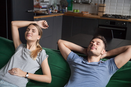 Young couple relaxing on comfortable sofa together breathing fresh air at home, calm carefree man and woman enjoying no stress free weekend and peaceful rest having healthy nap on daytime on couch