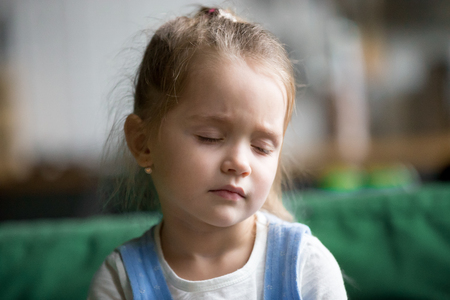 Headshot of upset little girl feeling pain, sad, tired or sleepy, frustrated depressed kid face suffering from sleep disorder, fatigue or having problem, dizzy child drowsy exhausted or bored concept