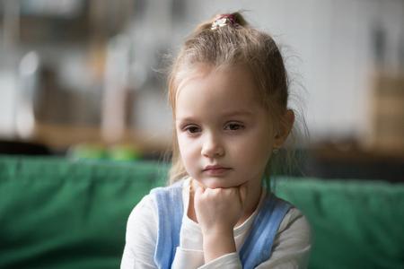 심각한 잠겨있는 영리한 귀여운 꼬마 소녀는 질문이있는 생각에서 길을 잃고, 사려 깊은 얼굴이 턱 밑에 손을 잡고 손을 잡고 호기심, 우울하거나 지루함을 느낍니다. 스톡 콘텐츠 - 105958544