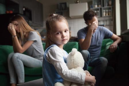 Bambina frustrata sconvolta stanca dei genitori litigano guardando la telecamera, ritratto della figlia di bambino prescolare triste soffre di litigi di famiglia mamma e papà o mancanza di attenzione, concetto di figlio e divorzio