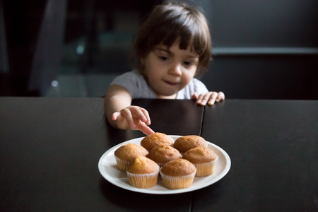 Cute curious little girl looking and reaching hand taking muffins on table, hungry funny kid eager to eat cake stealing cookie while parents not watching, bakery and child addiction to sweets concept Stock Photo