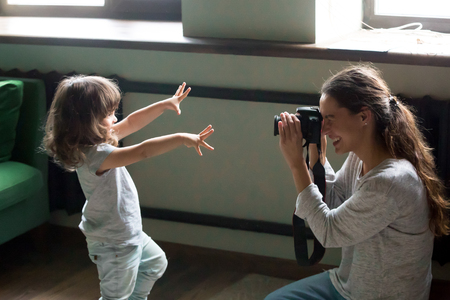 Mom photographer having fun playing making photo of artistic cute kid daughter at home, young mother photographing little child girl or shooting video on digital camera, funny family photo session