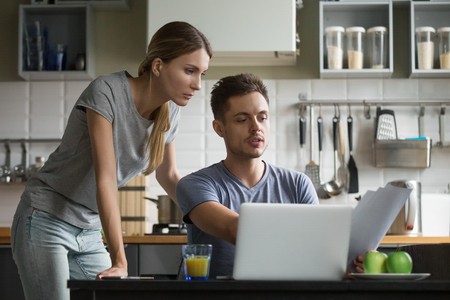 Young serious couple discussing papers with laptop, man and woman roommates or husband and wife checking rent or domestic bills to pay online, planning budget or analyzing financial expenses together