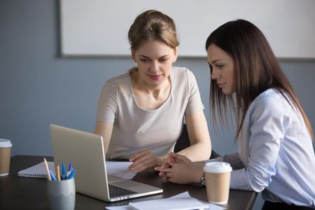 Colleghe che lavorano al computer portatile che negoziano sul progetto di affari nella sala riunioni, donne di affari che discutono dell'idea di avvio, amministratore delegato millenario che mostra le statistiche sul computer al partner o al collega