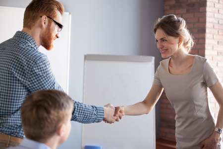 Millennial male worker shaking hand of smiling female partner or colleague during office meeting, businessman handshaking businesswoman greeting with success, employer congratulating applicant 스톡 콘텐츠