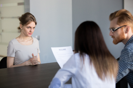 Worried female job candidate waiting for recruiters decision or questions, anxious about interview process, HR team reading employee resume, considering her candidature. Employment concept