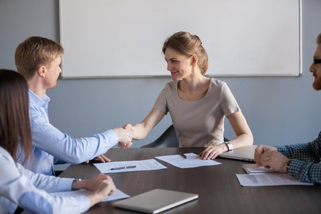 Female businesswoman shake hand of male colleague or partner, congratulating with contract sign, female ceo greet male worker with promotion or employment at office team meeting. Recruitment concept Stock Photo
