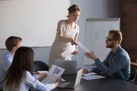La empresaria millennial entrega materiales de distribución a los miembros del equipo de trabajo durante la presentación del rotafolio, la oradora o entrenadora comparte documentos con los trabajadores, el presentador entrega documentos para considerar o analizar