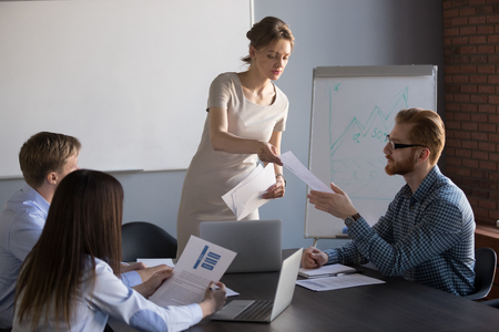 Millennial-zakenvrouw geeft hand-outmateriaal aan teamleden tijdens flip-overpresentatie, vrouwelijke spreker of coach deelt documenten met werknemers, handpapieren van presentator om te overwegen of te analyseren