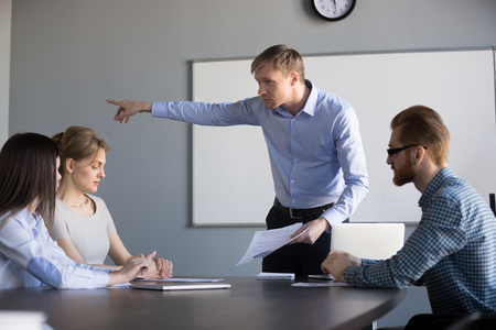 Mad businessman ask female worker leave company briefing because of bad work results or incompetent behavior, male boss fire employee, pointing on door, dismissing manager in boardroom Stock Photo