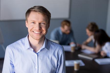 Retrato de sonriente empleado masculino de mediana edad posando durante la reunión del equipo de la empresa en la sala de juntas, empresario feliz y seguro mirando a puerta cerrada, haciendo una imagen para el catálogo corporativo durante la sesión informativa