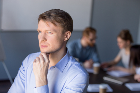 Thoughtful millennial businessman look far in distance, think about business plan and startup project, male employee dream about future success, consider goal achievement. Business vision concept
