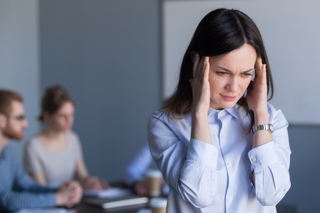 Stressed millennial woman suffer from headache during team business meeting, tired or frustrated female employee feel migraine or dizziness, not able to focus on work, worker avoiding loud voices