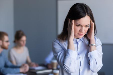 Une femme millénaire stressée souffre de maux de tête lors d'une réunion de travail d'équipe, une employée fatiguée ou frustrée ressent une migraine ou des étourdissements, ne peut pas se concentrer sur son travail, le travailleur évite les voix fortes