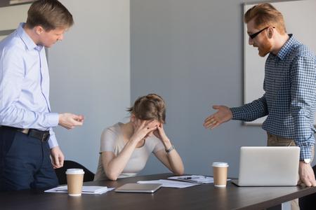 Männliche Kollegin, die eine depressive Arbeitnehmerin anschreit, sie für Dokumentenfehler verantwortlich macht, wütende Geschäftsleute, die die Geschäftsfrau anschreien und sie für das Scheitern oder den Absturz des Unternehmens schuldig machen