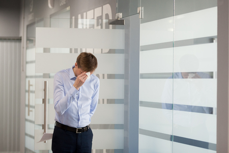 Nervous male employee wipe face sweating from worries before entering meeting room to make business presentation, frustrated worker scared to present company report for colleagues. Work stress concept