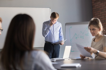 Stressed male speaker or presenter worried before making presentation for colleagues in meeting room, nervous employee wipe face scared to speak in public, afraid to present business report in office.
