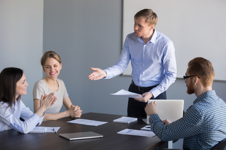 Millennial businessman talking to female worker during company briefing, complimenting for good work, male ceo greeting happy woman employee with high achievements and results at office meeting Standard-Bild