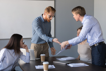 Angry male colleagues argue over contract conditions during company business meeting, mad workers dispute about document terms, millennial businessman disagree with coworker on paperwork issue