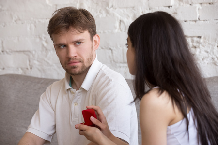 Decisive girlfriend making marriage proposal to frustrated boyfriend, presenting engagement ring, feminist woman asking surprised puzzled lover to marry, setting family. Feminism concept