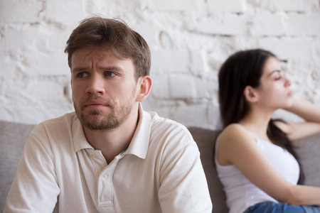 Upset millennial man think about relationship problems, having fight with proud female lover, offended couple not talking after family quarrel, sad male consider breaking up or divorce with girlfriend Archivio Fotografico