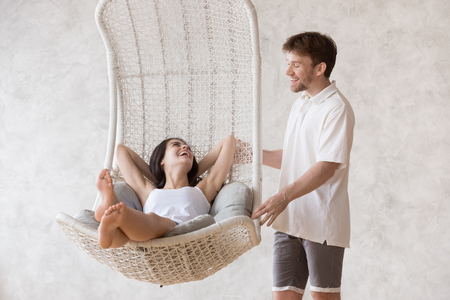 Smiling millennial boyfriend swing excited girlfriend in hanging lounge chair at home, happy woman relaxing in cozy suspended sofa while her lover dandle it, couple laughing having fun together Foto de archivo