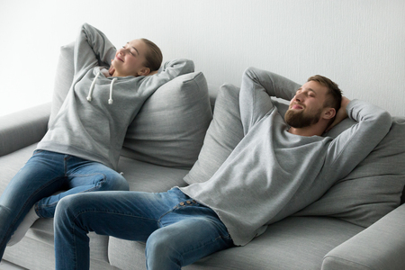 Happy millennial couple relax on cozy sofa taking nap at home, boyfriend and girlfriend stretch enjoying rest on comfortable couch, man and woman having break lying on new furniture with eyes closed
