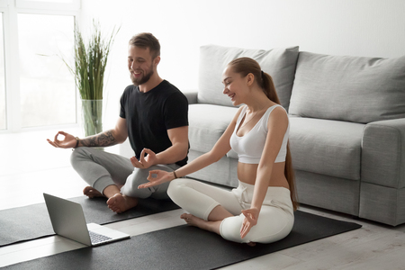 Smiling millennial couple practice yoga on mats at home watching video tutorial on laptop, excited man and woman sit in lotus position meditating repeating online instructions by coach on computer