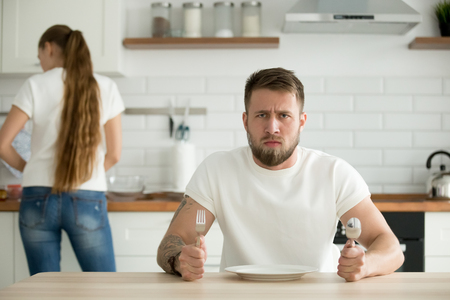 Dissatisfied hungry male impatiently waiting for dinner, mad man sitting at table with empty plate want to eat, busy wife prepare food for husband cooking dishes in kitchen. Gender inequality concept