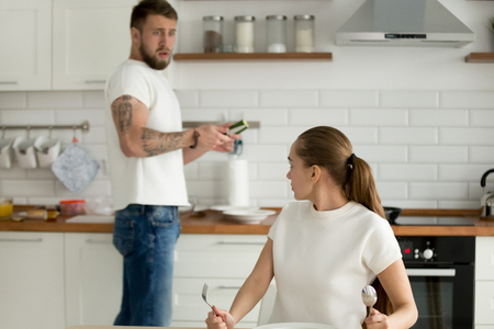 Mad funny girlfriend look dissatisfied scold boyfriend for bad dinner or breakfast, surprised man frustrated by wife food complaint, man cook dish at home kitchen. Concept of feminism, gender equality Stock Photo