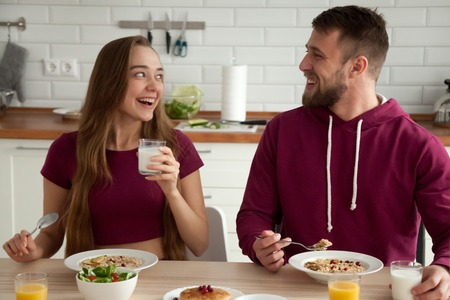 Happy young couple smiling enjoying delicious healthy oatmeal breakfast in kitchen, excited boyfriend and girlfriend eating tasty porridge, having homemade food, having fun in the morning at home Foto de archivo