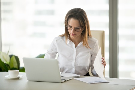 Serious business woman working with laptop documents analyzing project results, marketing plan or preparing financial report at workplace using computer online software for accounting data analysis Archivio Fotografico - 107343253
