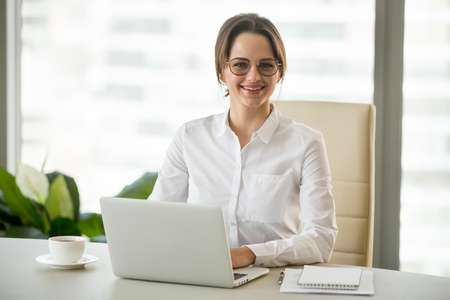 Smiling millennial businesswoman in glasses sitting at work desk with laptop, friendly professional looking at camera at workplace, female boss, company executive or successful entrepreneur portrait