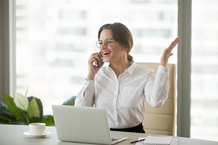 Happy businesswoman excited about hearing good news talking on cell phone in office, smiling emotional woman speaking by mobile at work motivated by amazing business win or great surprise