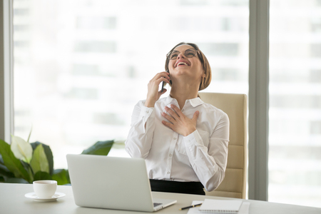 Happy millennial businesswoman laughing having funny conversation talking on phone in office, delighted woman excited or pleased about good news being promoted speaking on cellphone at work break
