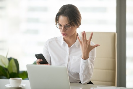 Angry outraged businesswoman annoyed with missed call or no signal on stuck not working mobile phone in office, furious frustrated employee holding cellphone feeling mad about spam bad message